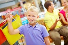 Portrait of happy boy with paperbag looking at camera with his parents behind Stock Photo