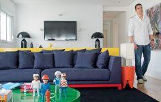 O designer de interiores Diogo Oliveira projetou um painel amarelo para esconder as costas do sofá. Com estofado azul e pés vermelhos, ele faz uma composição colorida