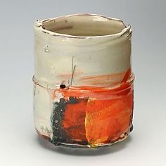 This is a thrown and marked slipware pot by Barry Stedman using a red earthenware body. The pot has then been covered in a white slip and decorate with orange yellow and black slips.