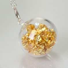 Gold leaf in hand blown glass silver plated necklace by TheStudio8, via Etsy.