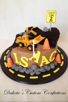 """Construction Zone Birthday Cake - I made this cake for a 2nd birthday.  Construction cakes can end up being kind of boring so I tried to add as much interest as I could:)  Chocolate buttercream with Oreo cookie """"dirt"""" and fondant accents including the sign, rope, traffic cones, rocks and road. The only things not edible were the vehicles which were provided by the client.  Thanks for looking!"""
