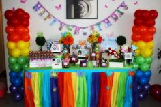 Rainbow Party Theme.  Tie balloons to a PVC pipe anchored in an umbrella stand and the fantastic table skirt is made from gathered plastic tablecloths.