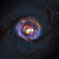 Surprising Spiral Structure Found at Galaxy's Supermassive Black Hole: The image above shows the central parts of the nearby active galaxy NGC 1433. The dim blue background image, showing the central dust lanes of this galaxy, comes from the NASA/ESA Hubble Space Telescope. The colored structures near the center are from recent ALMA observations that have revealed a spiral shape, as well as an unexpected outflow, for the first time.