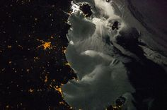 Moonglint Over Italy. (Archive 2013.10.17) This soft-focus image taken by a crew member aboard the International Space Station during Expedition 37 shows the Elba-Follonica-Grosseto-Orbetello area of Italy at night, with moonglint on the surrounding waters. (ICredit: NASA)