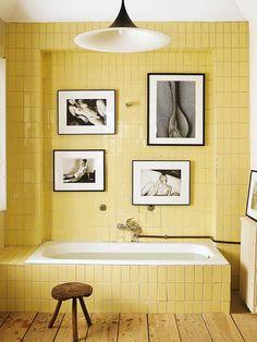 fotografias e azulejo amarelo em banheiro
