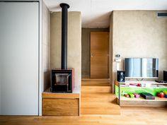 Atmosféru v obývacím pokoji dotváří krbová kamna, dveře nad schůdky vedou na toaletu - ProŽeny.cz
