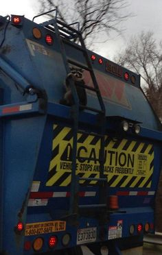 Raccoon holding on for dear life on the back of a garbage truck.