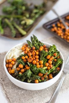 Harissa roasted chickpea bowls - with crispy roasted asparagus, broccoli and kale! The crispy, spicy roasted chickpeas are the perfect contrast with the smooth and creamy mashed potato. So good! Vegetarian, gluten-free, and easily made vegan.