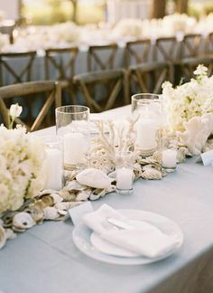 Flowing white vintage linen used on tables for the reception with white sea shells and coral down the middle
