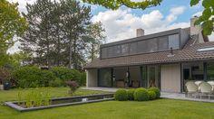 De villa is omringd door een grote groene tuin met langgerekte vijver en overdekt terras onder het overstek.