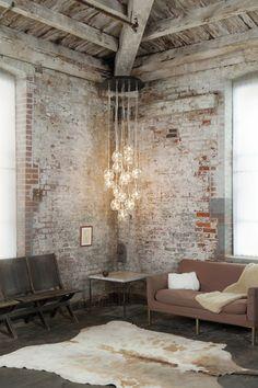 John Pomp Studios - Brand - Industrial - Exposed Brick - Fur Rug - Fur Throw - Wood - Neutrals - Dangling Lights - Living Room