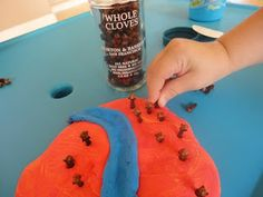 Pushing whole cloves into playdough for a sensory/fine-motor activity that smells great.