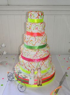 6 tier wedding cake - 5 tiers are cake, the bottom tier is a dummy. Fondant bride & groom, wire tandem bicycle - as the groom owns a cycle shop and proposed to the bride on a tandem ride :) 6 Tier Wedding Cakes, Bride Groom, Fondant, Dream Wedding, Lily, Neon, Desserts, Paint, Weddings