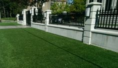 Security fencing and gates sitting on top of a concrete wall. This is artificial turf for lawn. (It has come a long way)
