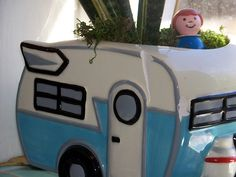 Retro-looking camper planter!  With Fisher Price person peeking out!  This makes me smile. :)