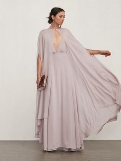 It's your day - put your bridesmaids in full length capes if you want to. We promise, they won't be mad. The Doris Cape is a chic, sheer georgette cape with a hook/eye closure at the neck. It tapers down the front and there are arm openings at the side so it's easy to slip into and out of. Your friends can wear it at the ceremony to look a bit more formal, then lose it at the reception to show a bit more skin. Made from 100% viscose.