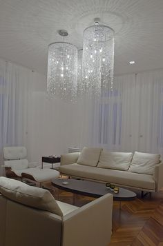 Unique chandeliers add character to a simple and clean living space