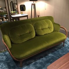 Porada's trademark wood has been updated with jewel-bright velvets and upholstered buttons