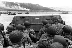 American assault troops in a landing craft huddle behind the protective front of the craft as it nears a beachhead, on the Northern Coast of France. Smoke in the background is the Naval gunfire supporting the land, June 6, 1944.