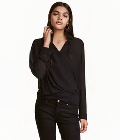 Black. Blouse in airy crêped chiffon. Collar, wrapover front with concealed hook-and-eye fastener, and buttons at cuffs. Longer at back.