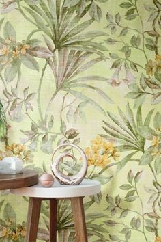 A beautiful floral wallpaper featuring growing palm leaves with entwined yellow and white blooming flowers; all displayed in a faded watercolour effect.