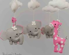 Welcome to Taylored Whimsy! Where custom, couture baby mobiles are lovingly created for your special little bundle of joy. To provide you with a mobile totally unique to your little one mobiles are custom made and not ready to ship - as of this date ship estimated ship time is 4-6 weeks from payment date. FELTIES INCLUDED: 3 Elephants, 2 Giraffes, 5 Clouds MOBILE COLOR CHOICES: The colors of the listed elephant and giraffe mobile are: cyan and silver. Coordinating fabrics are used for the…