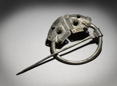 Silver bossed penannular brooch, each terminal with 5 bosses and incised interlaced zoomorphic design.