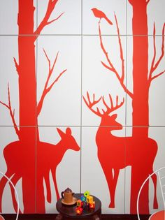 Adding a focal point was a main design element for Evander and Frankie's bedroom. By installing ready-made kitchen cabinets to the wall, then adding graphic interest with vinyl decals in the shape of a fawn and a buck in the forest, the twins have concealed storage that also doubles as an art installation.