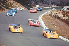 1970 Laguna Seca, two orange McLaren Can-Am cars in the lead.