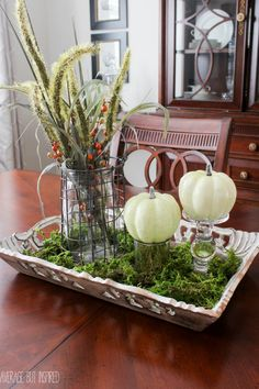 As part of the Fall-oween home tour, Average But Inspired takes you on a tour of her home decked out for fall and Halloween. This simple fall centerpiece is a snap to put together with dried moss, faux cattails, and faux pumpkins.
