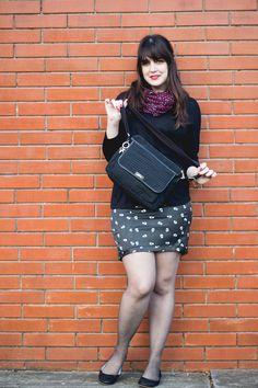 Look com peças pretas com saia lápis com estampa de caveiras sapatilha e bolsa da kipling