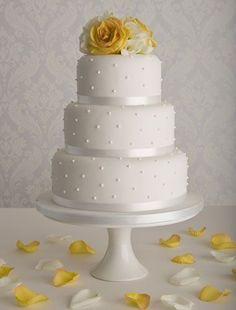 Simple three-tiered white wedding cake with polka dots and flowers on top #wedding #weddingcake #cake #polkadots #yellow