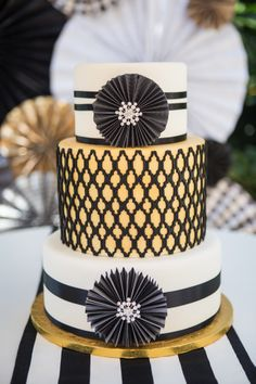 - Black, white, and gold wedding cake incorporating the paper wheels and some bling with a quatrefoil center tier.