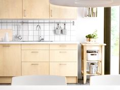 FAKTUM kitchen with NEXUS birch veneer doors/drawers, PRÄGE white worktop and BEKVÄM solid birch kitchen trolley