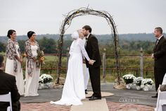 You may now kiss the bride! Grapevine arch decorated by Von Jakob. Photo by Carter's Photography.