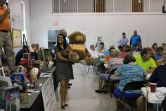 """Cyerra Davis hold up a teddy bear prop from the TV show """"Big Brother"""" during the live auction part of the Boys & Girls Club celebrity Auction held in August 2016 at Trinity United Methodist Church in Greeneville, Tennessee"""
