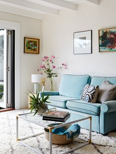 Blue sofa, Moroccan shag rug, brass coffee table in the home of writer/performers Sarah Collins and Justin Kennedy.