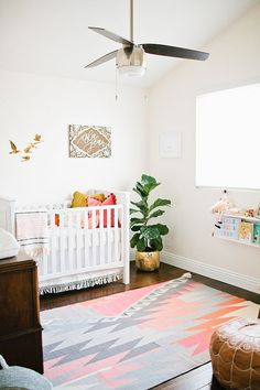 Nursery with pops of color - white walls, pink and gray carpet, pink cushion, wall-mounted kids bookshelves
