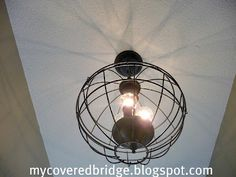 Ballard orb light fixture knockoff for $10 (two wire plant hanging baskets) - WHAT AN AWESOME IDEA!! (I must admit I am a little over Mason Jar lights!!) NICE CHANGE, OUI!!