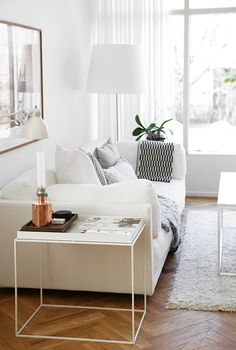 Trendenser - white sofa, white side table, white shag rug and lamp, with black & white cushions for contrast.