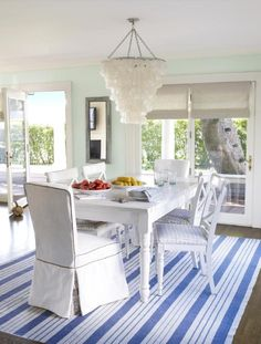 Blue and White Dining Area: Coastal A combo of slipcovered seats and cushioned X-back chairs is more casual than a matching set. The table's antique white finish gives it a slightly weathered look. HGTV