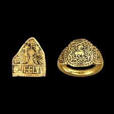 Æthelwulf ring: Wiltshire, AD 828-58: Triangular bezel depicting stylized plant motif between two birds. The hoop decorated with a quatrefoil and interlaced knot design.  Æthelswith ring: West Yorkshire: Circular bezel with a beaded frame and contains a cruciform filled with leaf motifs. Within a central circle is a charming four-legged animal with a halo and the letters A and D which stand for 'Agnus Dei' (Lamb of God).  The ornament on both rings is inlaid with niello to make it stand out.