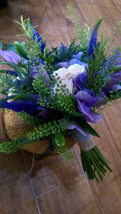 Blue toned bridal bouquet with green bell foliage, veronica, hydrangea, blue thistle, lisianthus and spray roses.