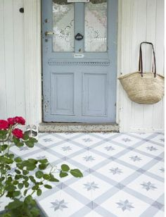 lace on the window, blue door, blue and white tiles and roses in the foreground; this is a lovely photo!
