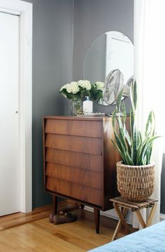 plant and stool next to a tall drawer. Mirror behind it, and accessories