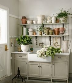 When is a mud room not used for mud? When it's transformed into a potting area instead.  Beautiful garden sink and cabinetry along with purposeful, well-stocked shelves.