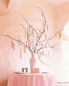 """For a guest book, this couplefollowed a Japanese custom by asking guests to tie their sentiments to tree branches with ribbons. The branches were adorned with crepe-paper buds and blossoms and placed in a porcelain vase. Expressions like """"Prosperity"""" and """"Good Marriage"""" were written in Korean and Japanese and hung ahead of time to decorate the branches."""