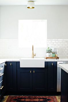 Navy cabinets, white counters, and brass fixtures for a fresh look.