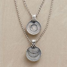 SILVER LUNA/SOL NECKLACE--This necklace displays two granulated sterling disks—one emblazoned with a sun, the other with a moon—suspended from two chains of different lengths