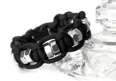 Rugged, masculine fidget bracelets give boys and men a fidget to unobtrusively carry with them. Black paracord with hex nuts that spin and provide texture make for cool fidget jewelry that gives sensory input. Keeping fingers busy helps minds calm and focus. The perfect fidget for guys with autism, ADHD, or sensory processing disorder. Bracelet is pictured on a 13-year-old boy. Size of bracelet = wrist size; some slack is built in for comfort, so order size according to actual wrist si...